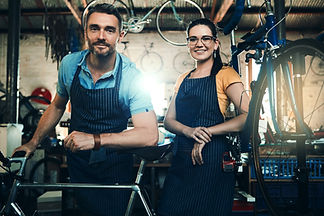 male and female bicycle mechanic models in a bicycle shop