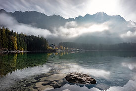 Mansion in the distance in front of tall, cloud covered mountains in front of a calm and snowy lake