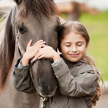 A young girl hugs the therapy horse she is working with during a session