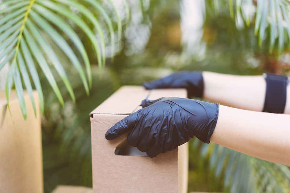 Delivery person with black rubber gloves delivering box.