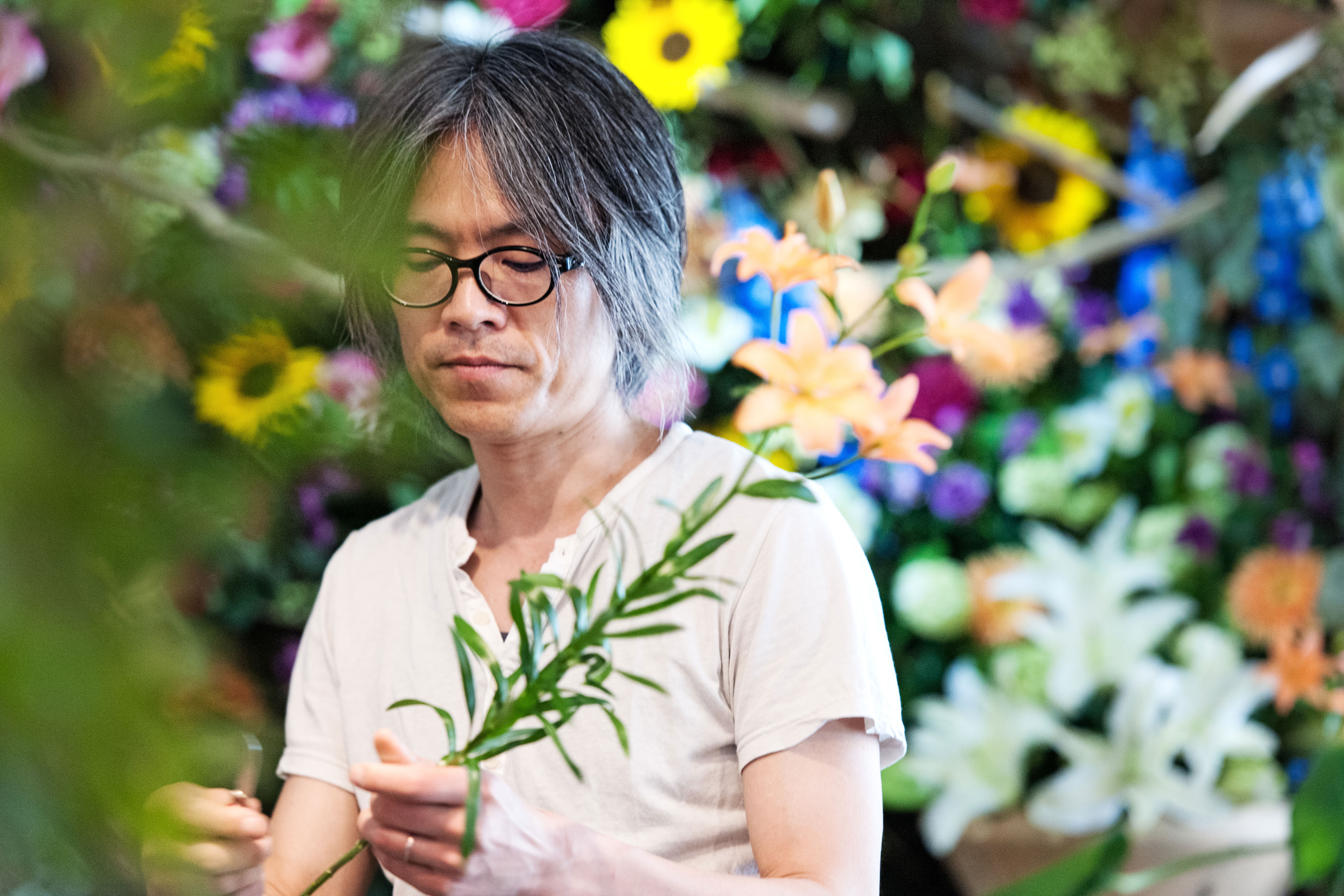 An older person wearing eye glasses concentrates while holding flowers in a floral shop