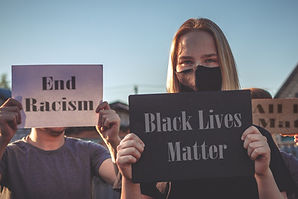Two people standing outside. The blonde female has a sign that states Black Lives Matter and the other person is holding a sign in front of their face that states End racisim.