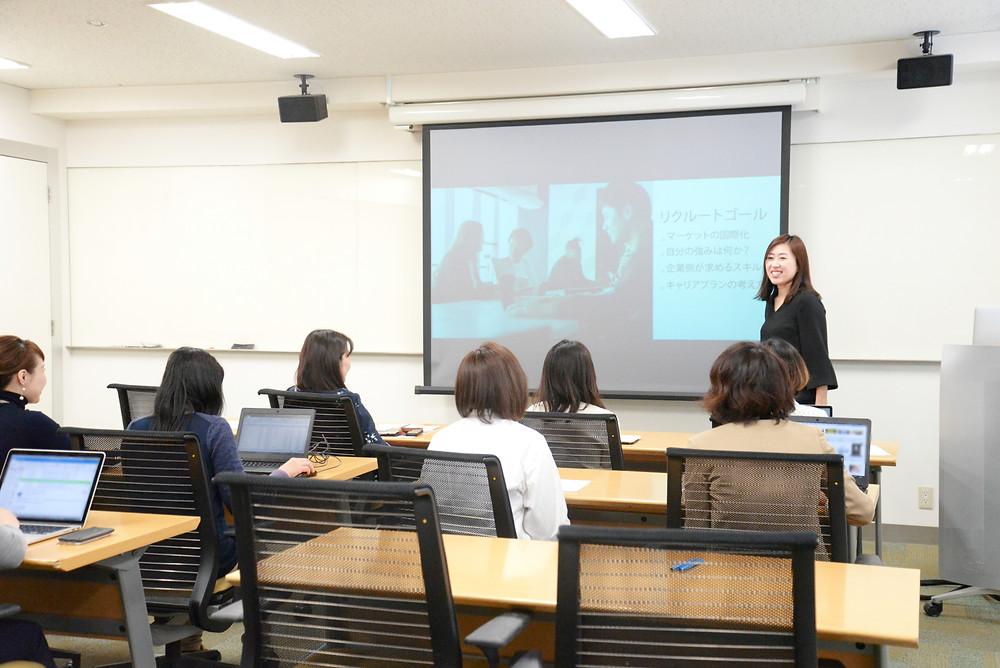 woman in front of screen showing images to people