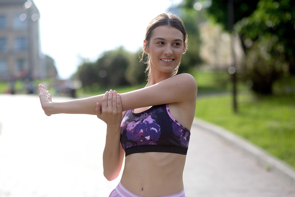 woman in fitness gear stretching before a run