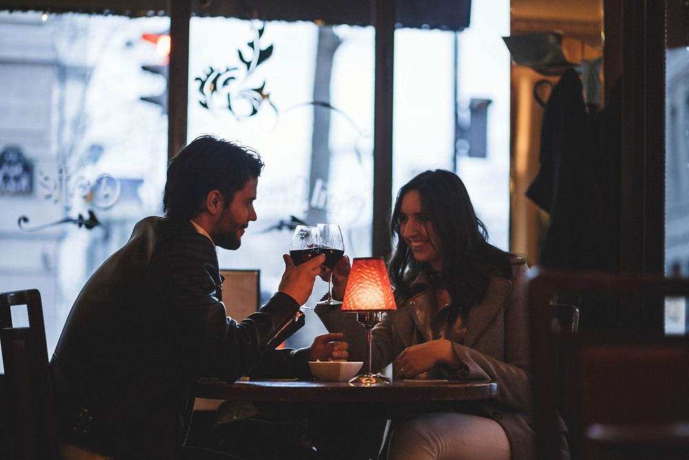 Man and a women sitting in an initimitely lit restaurant clinking glasses of wine together