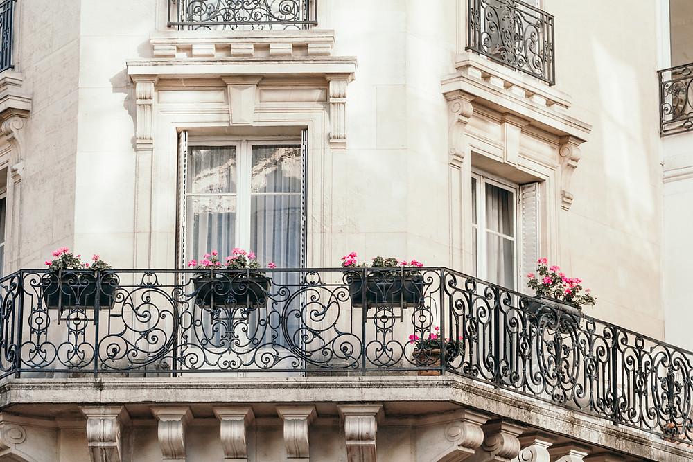 Façade d'un bel immeuble parisien avec rambarde en fer forgé et géraniums