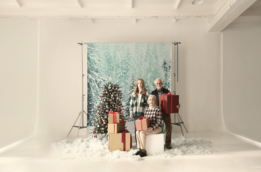 a family poses for a Christmas photoshoot in a studio