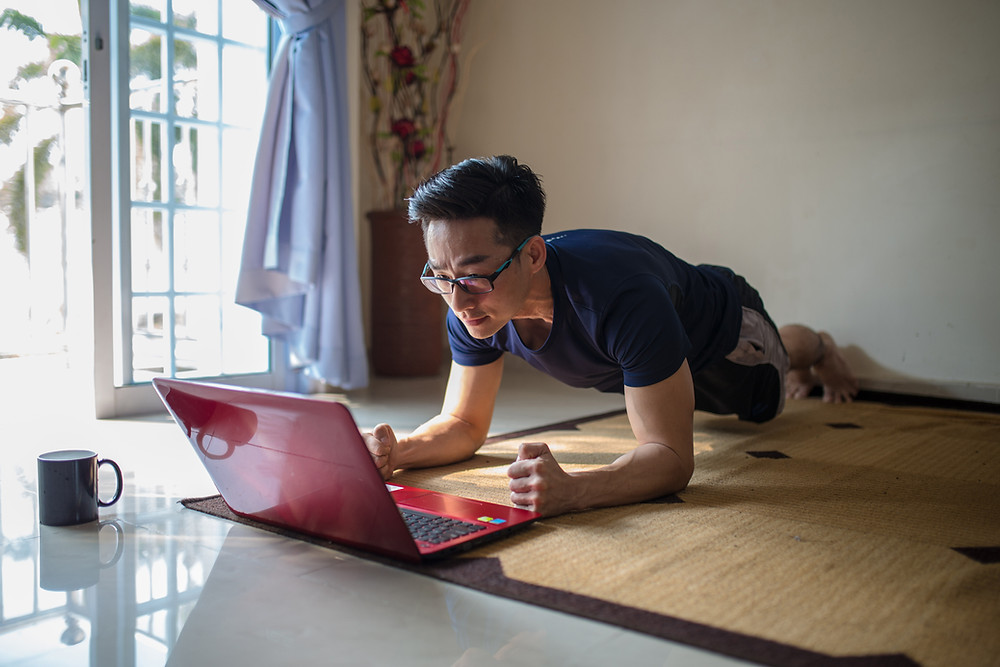 Man training indoors, watching an online fitness class on a red laptop.