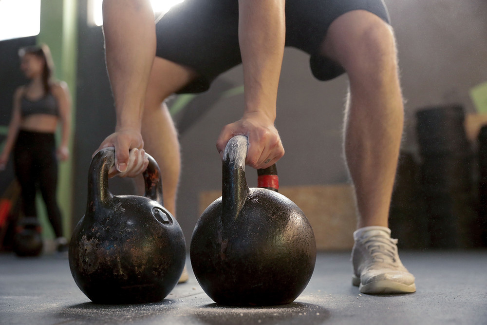 a man holding two heavy kettlebells about initiate the long cycle