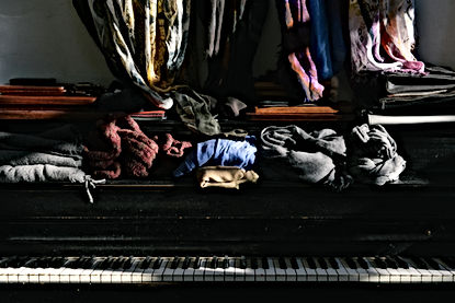Piles of Clothes on a Piano