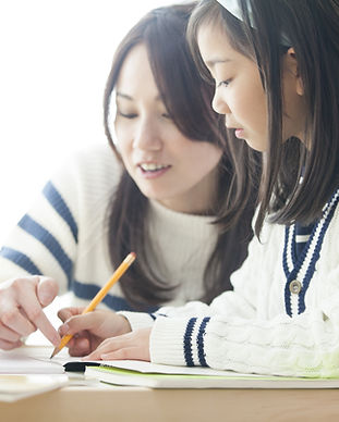 Tutor teaches PSLE English to a young girl in Singapore