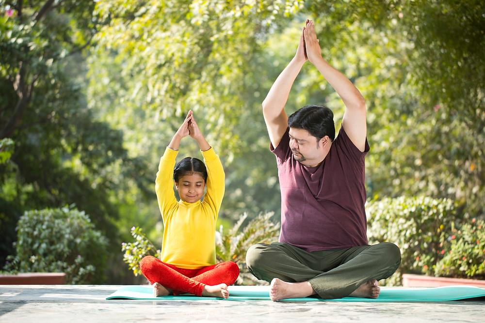 child and man doing yoga