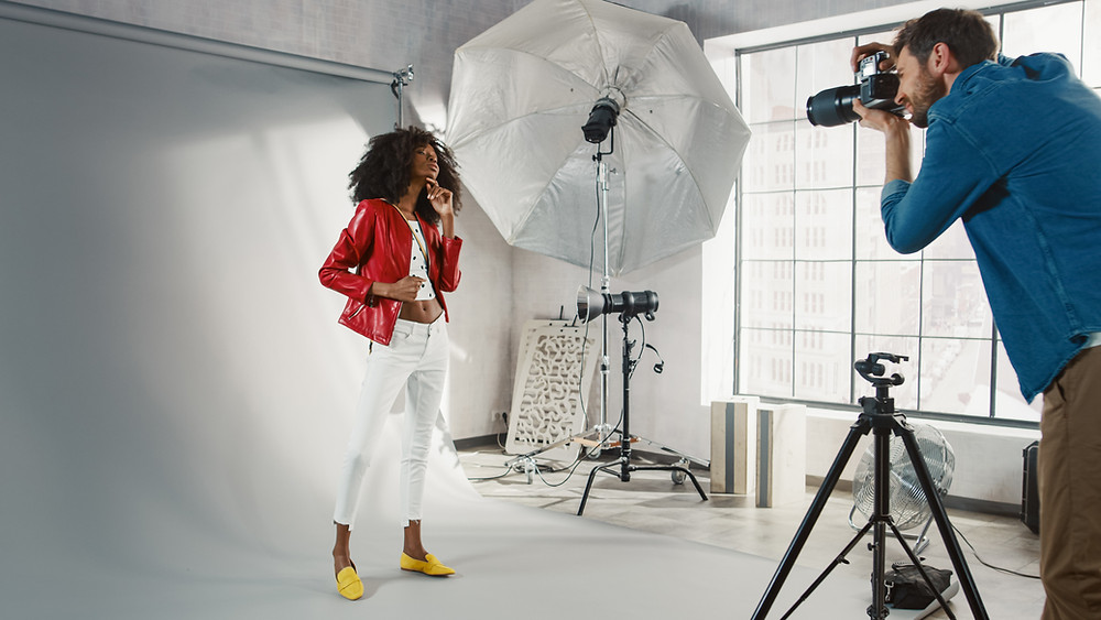 Photographer shooting a model in a studio