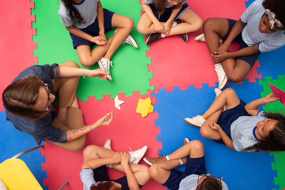 A teacher and 6 kids sitting on a play mat having a discussion.