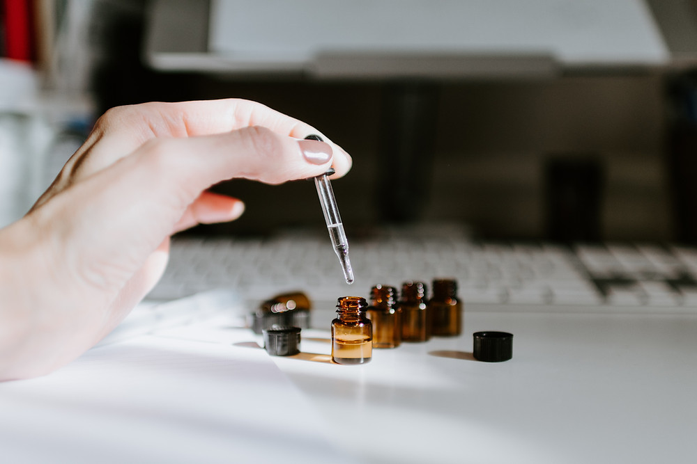 A woman holding a dropper over a bottle of essential oils