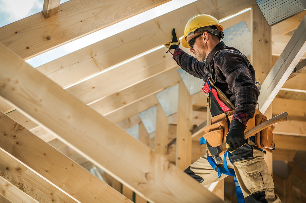 A construction worker putting house joists in place.