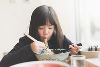 A girl eating noodles from a bowl using chopsticks