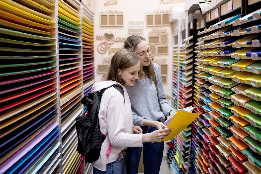 Two girls shopping at a craft store for colored paper