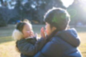 娘を抱っこする母親