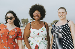 3 friends on a beach wearing sundresses and looking off into the distance