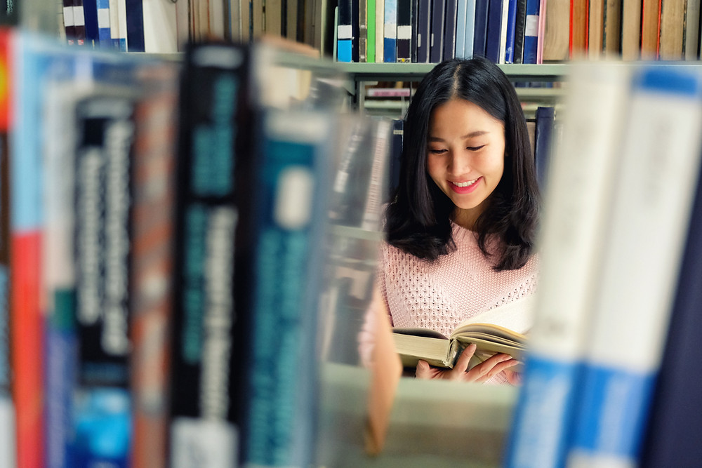 Student reads an encyclopaedia in the library in Singapore