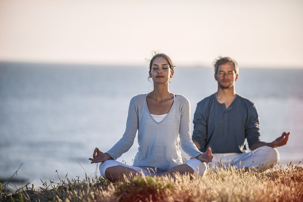 Woman & man sitting with legs crossed meditating with eyes closed in nature