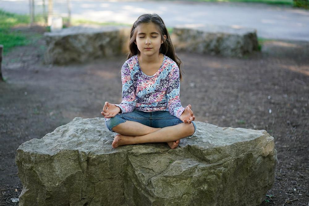 une fille en méditation sur une roche