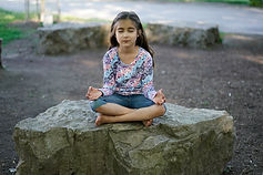 Girl with eyes closed mindfully meditating
