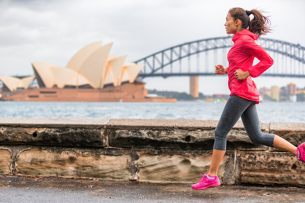 lady running beside Sydney Harbour with the Opera House in the background