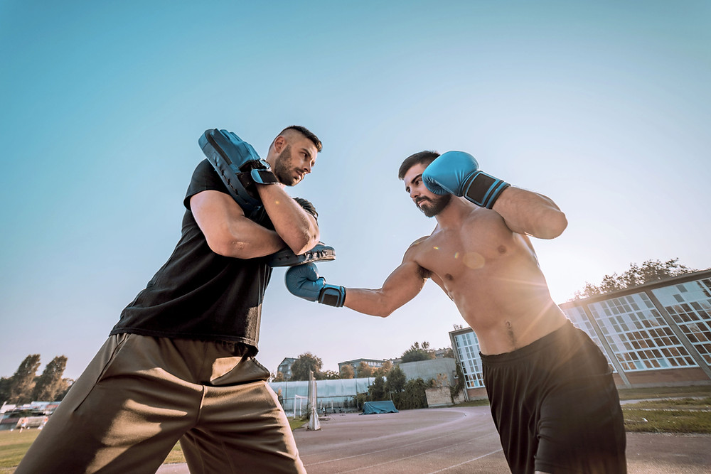 Two guys training boxing outside. One is holding the focus pads and the other is throwing punches. This image is supposed to illustrate the importance of pad training for the development of boxing skills.