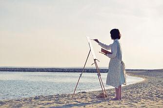 ビーチで絵を描く女性
