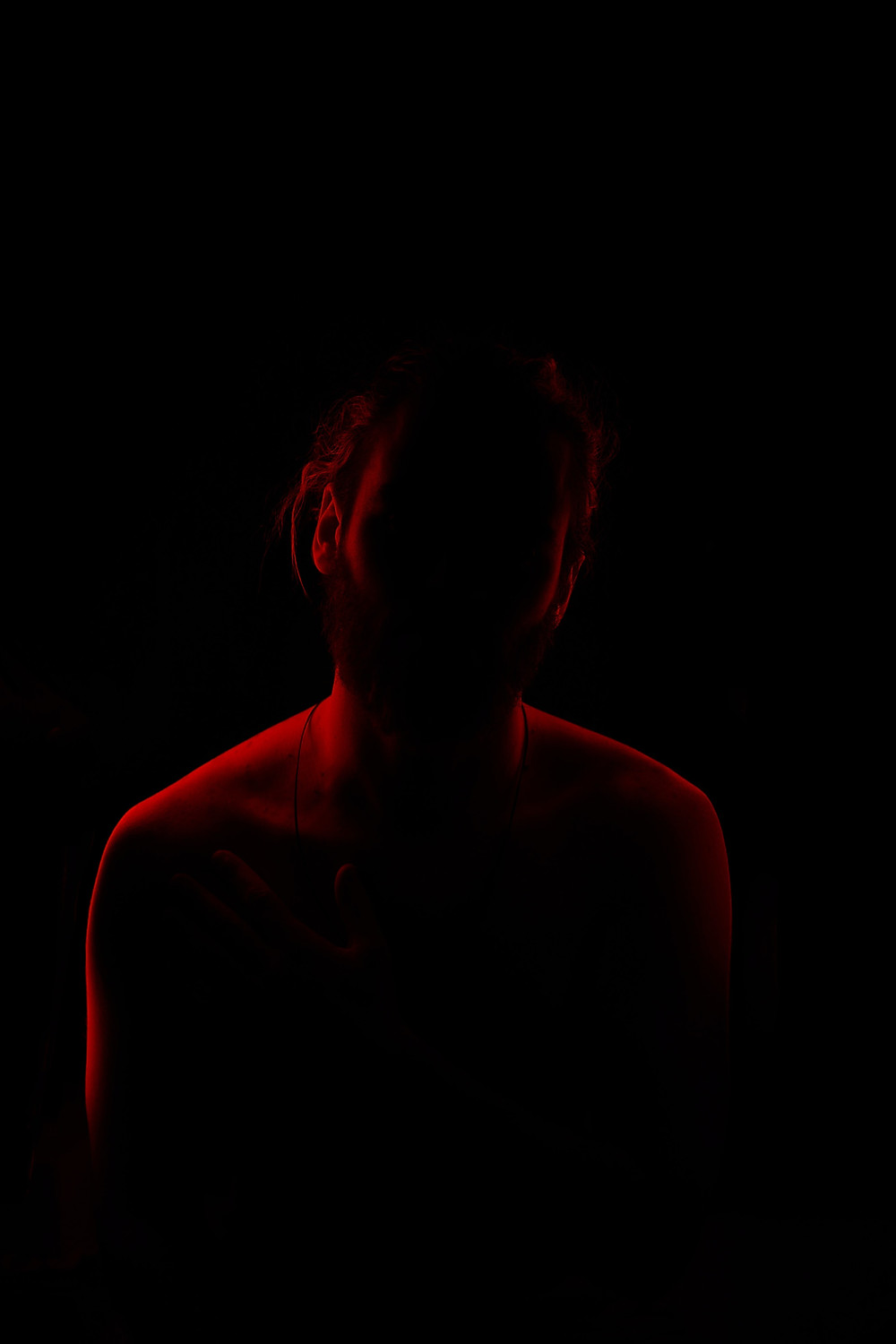 This is a red-light, dark silhouette of a shirtless male. His face is in shadow, only his shoulders are limned by backlight.