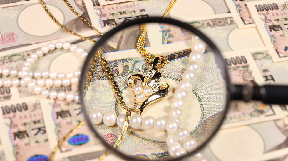 一万円札と拡大鏡と宝飾品