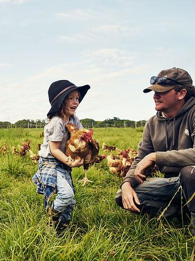 Padre e hijo en granja de pollos