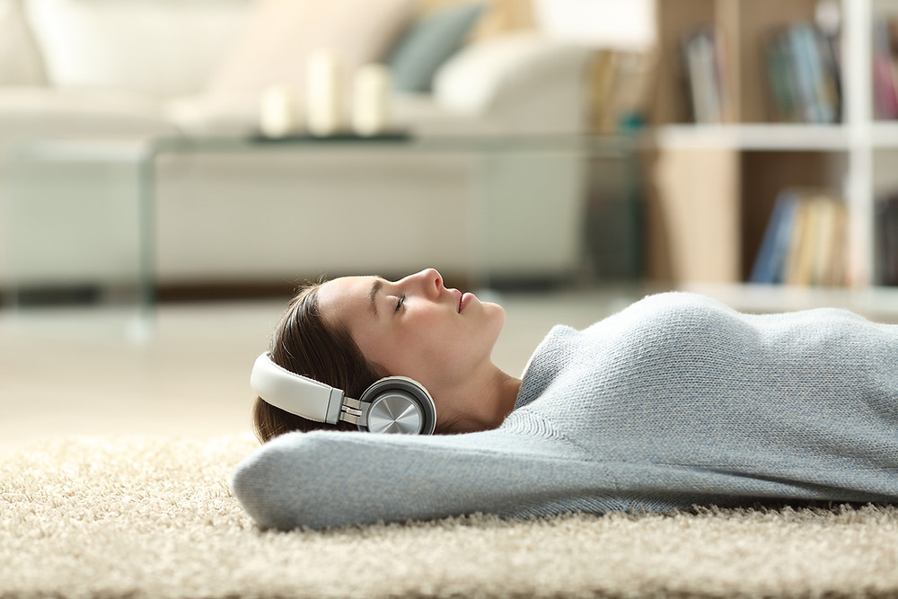 A woman lying on the floor of a house, listening to music with headphones on.