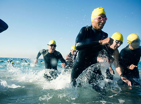 Swimmers running out of the water