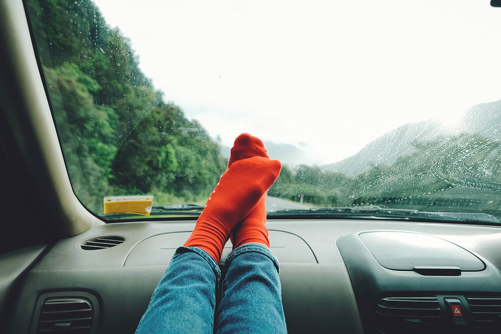 feet in colourful socks up on the dash of the car