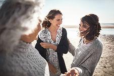 Frau lachend mit Freunden am Strandspazierend, als visuelle unterstützung für den Erfahrungsbericht der Schamanichen arbeit von Kuyay Lorena