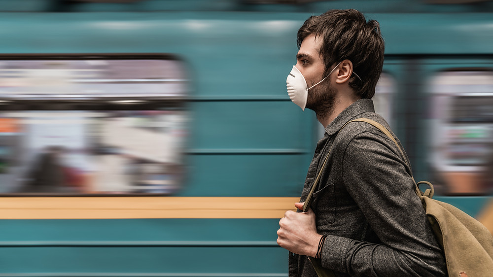 Man wearing mask, walking beside a moving train.