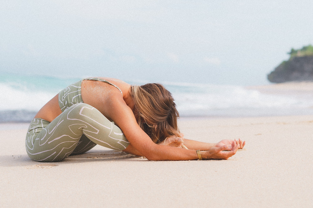 woman doing a relaxation yoga pose on the beach