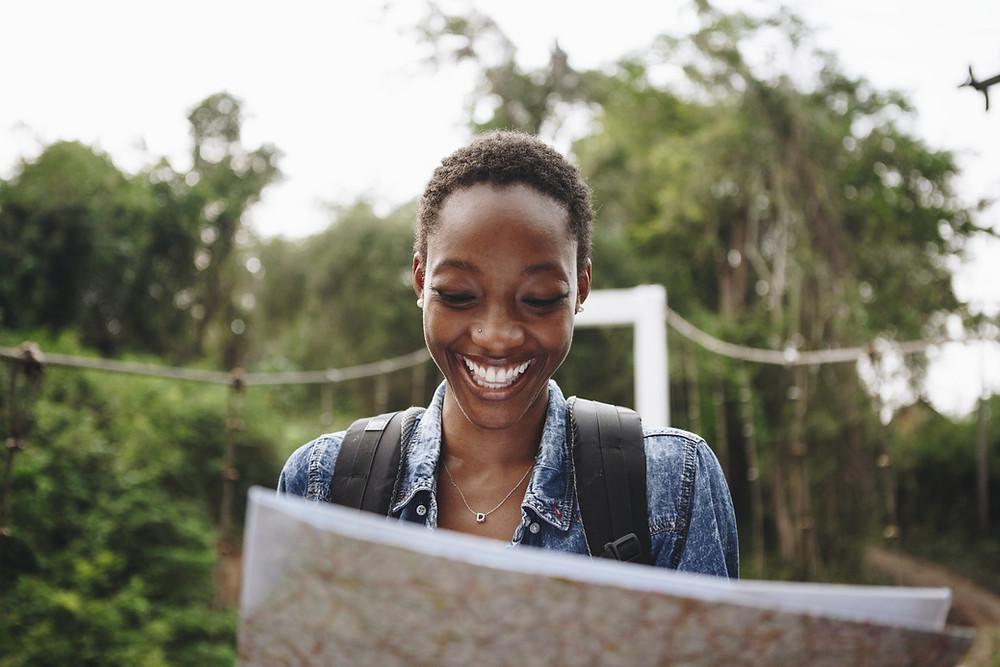 Touristin blicket lachend auf eine Karte.