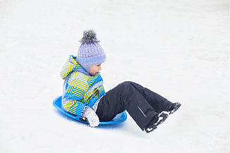 Girl Sledding in Snow