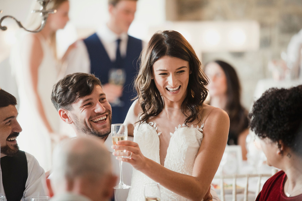 A portrait of the happy bride drinking champagne
