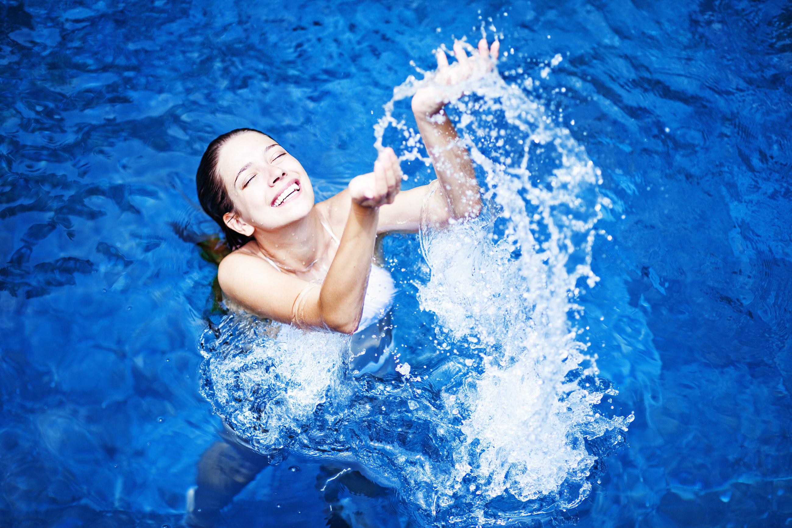 Woman splashing in pool