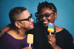 A queer couple wearing glasses smiling at each other holding rainbow popsicles