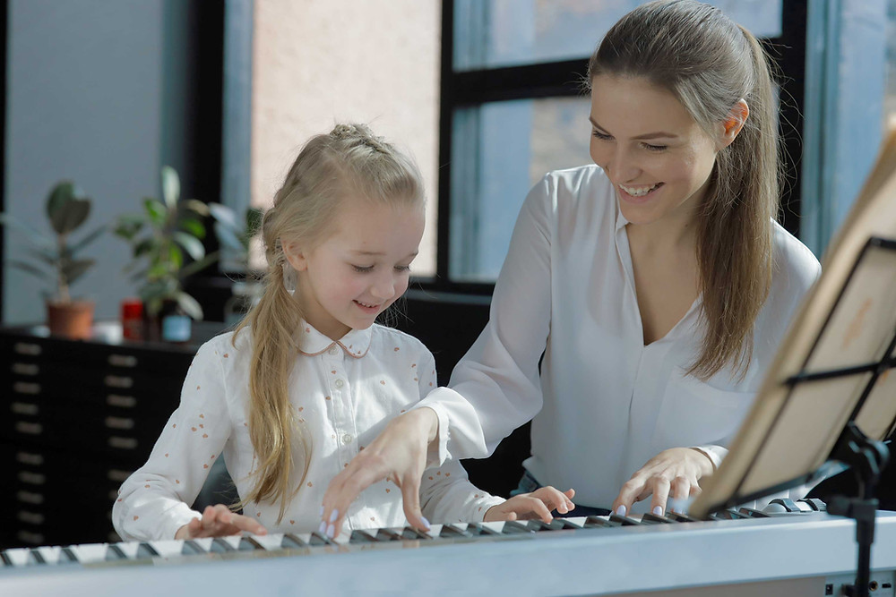 a female piano teacher giving piano lessons to a girl