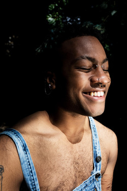 Young person with facial piercing smiling with eyes closed