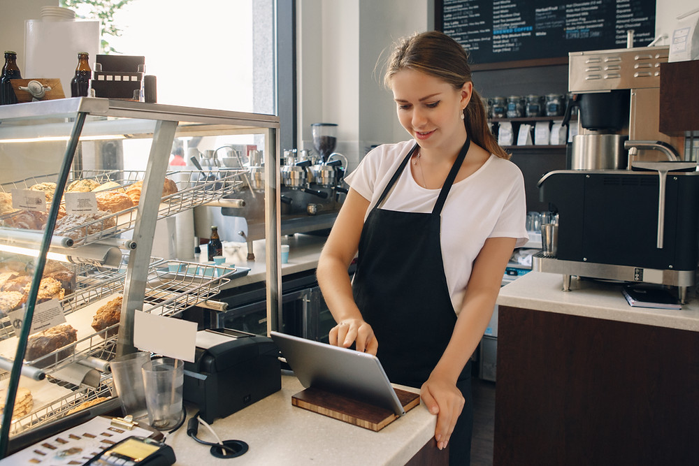female cashier using a tablet at a bakery to check out a customer