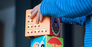 Child in blue striped long sleeve shirt stacking an orange box on top of blue and green box.