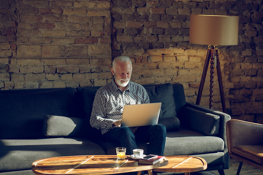 Older gentleman on his laptop reviewing his finances smiling and relaxed Paisley UK